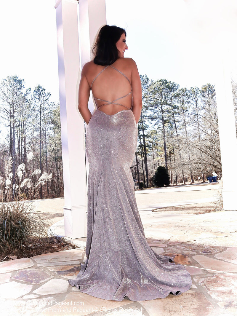 Back of Model in a nude prom dress featuring a plunging v neckline, slit, open strappy back and glitter everywhere. Perfect for PROM! And it's at Rsvp Prom and Pageant, your source for the HOTTEST Prom and Pageant Dresses and exclusive evening gowns and located in Atlanta, Georgia!