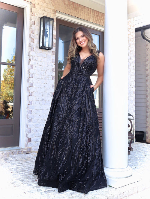 Brunette Model in this black ball gown which is perfect for senior prom with the v neckline and sequins all over, you will shimmer and sparkle all night! Not to mention, it has POCKETS! And it's at Rsvp Prom and Pageant, your source for the HOTTEST Prom and Pageant Dresses and Exclusive Evening Gowns and located in Atlanta, Georgia!