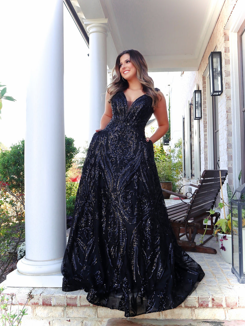 Pretty Model in this black ball gown which is perfect for senior prom with the v neckline and sequins all over, you will shimmer and sparkle all night! Not to mention, it has POCKETS! And it's at Rsvp Prom and Pageant, your source for the HOTTEST Prom and Pageant Dresses and Exclusive Evening Gowns and located in Atlanta, Georgia!