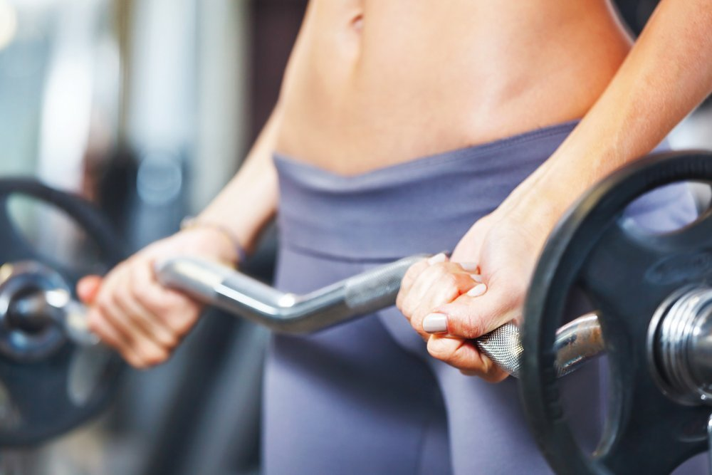 fit women lifts barbell