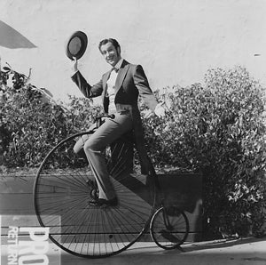Vincent Price on a bicycle on the Up in Central Park movie set