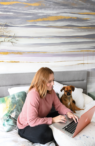 Dana Mooney, Vancouver Artist, works from home in her bedroom with her puppy by her side.  A custom wall mural creates a creative, calming bedroom oasis.