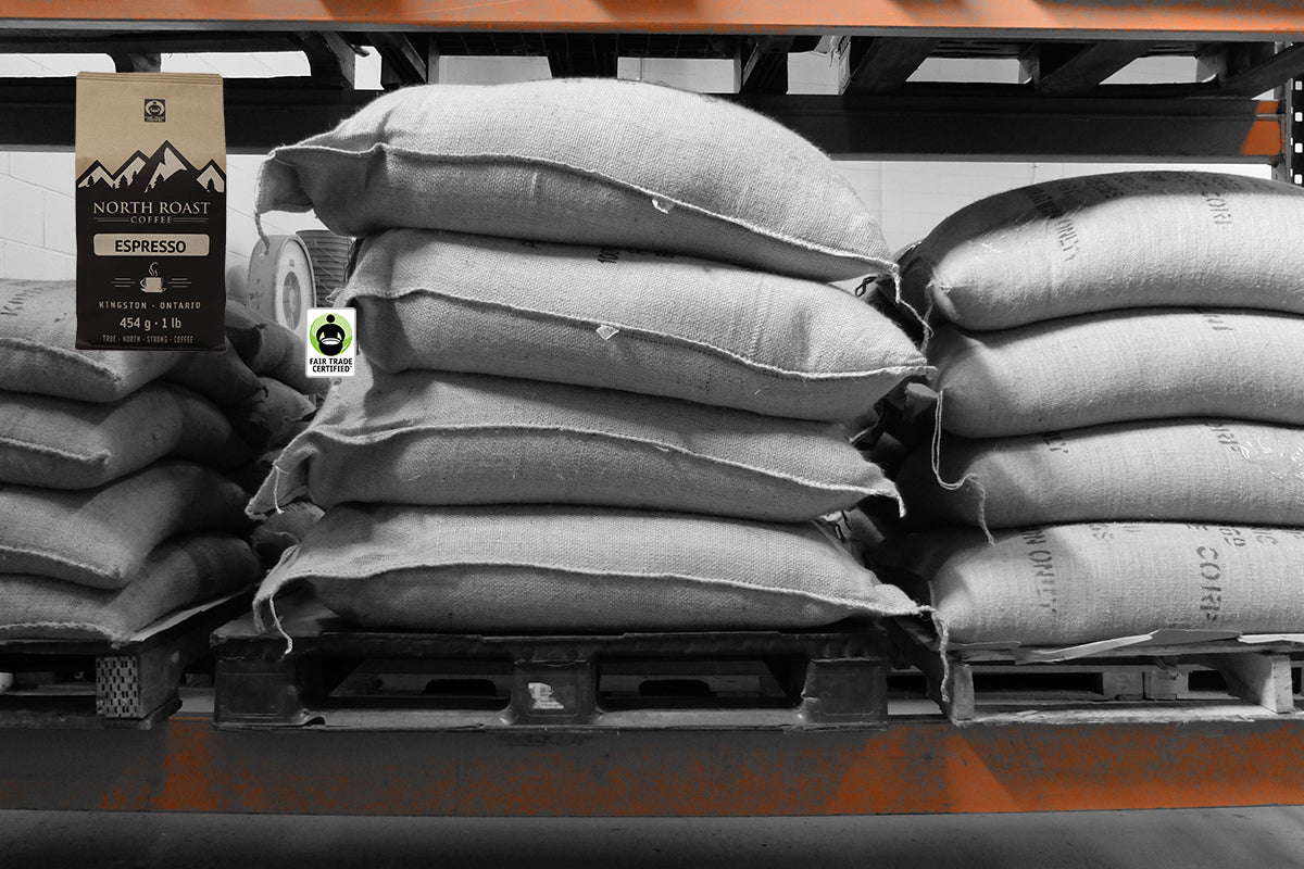 Pallets of green coffee are stacked on racks ready to be loaded into a coffee roaster.  A compostable North Roast coffee bag is placed in the top left corner of the image along with a Fair Trade Certified Logo
