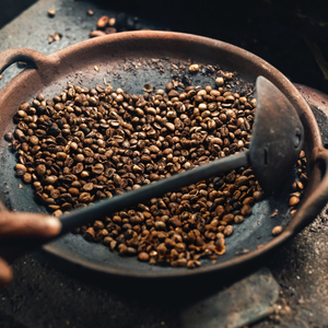 coffee beans roasting in large circular pan with ladel