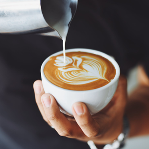 hands pouring latte art into cup