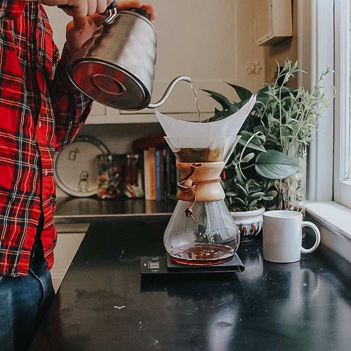 man wearing plaid shirt pouring hot water into chemex