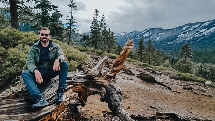 man sitting on drift wood in mountains