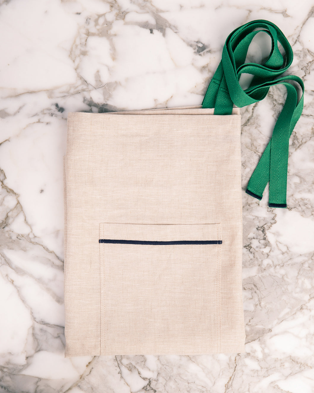 Premium beige linen half apron with navy blue pocket stitching and green adjustable ties.