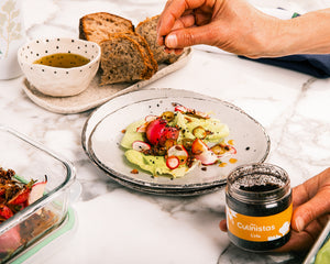 Chef sprinkling Culinista spice 'Urfa' on a salad next to bread with everyday Greek olive oil and meal prepped food