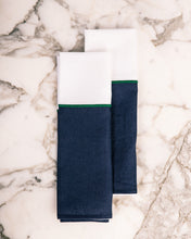 Load image into Gallery viewer, Two premium white and navy blue kitchen linens with green stitching detail.