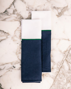 Two premium white and navy blue kitchen linens with green stitching detail.