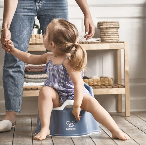 Girl sitting on a Baby Bjorn Potty Chair in Deep Blue