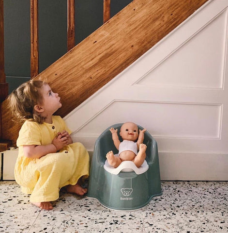 Little girl sitting next to her potty with a dolly sitting on it