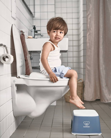 Boy sitting on a toilet with a Baby Bjorn Step Stool under his feet
