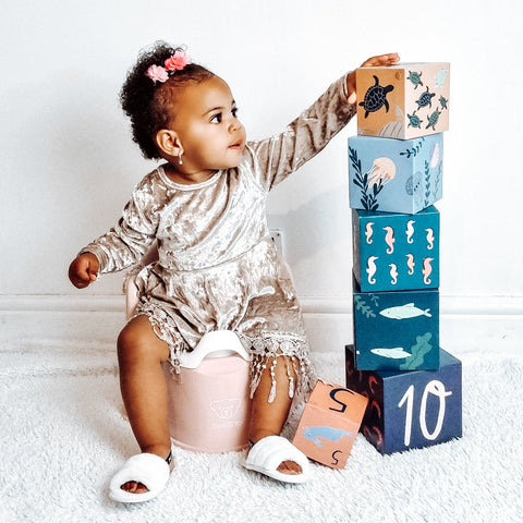 Little girl sitting on a Baby Bjorn Potty Chair playing with blocks