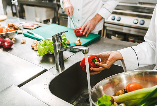 cropped view of female chef washing pepper in restaurant kitchen