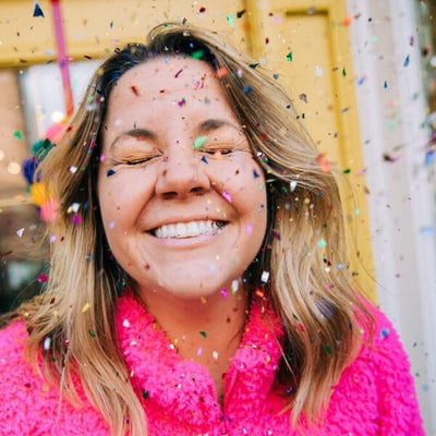 Cheerful woman wearing bright pink fuzzy sweater smiling with confetti in her face