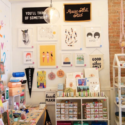 In-store display of shop wall featuring various prints and artwork by Canadian artists