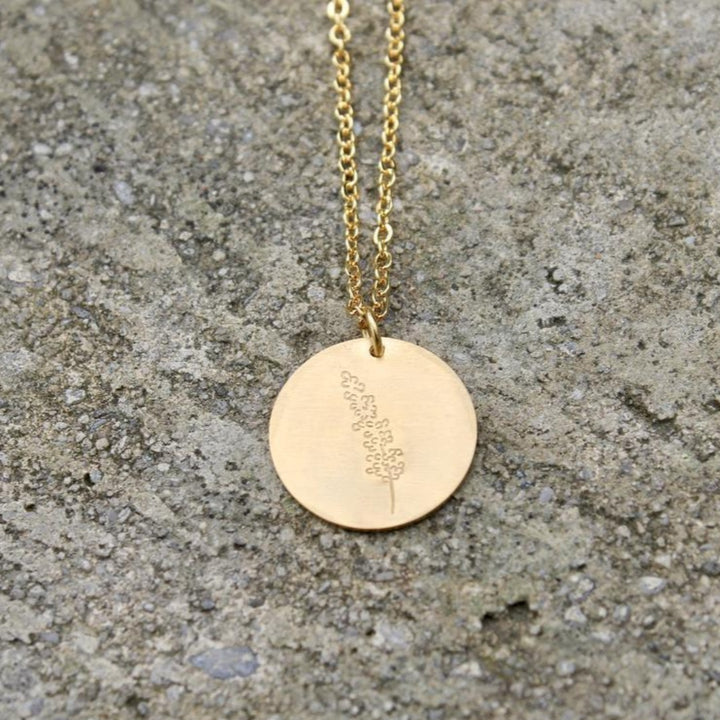 A close up of a gold pendant necklace with lavender engraved on it by Vintage Acorn