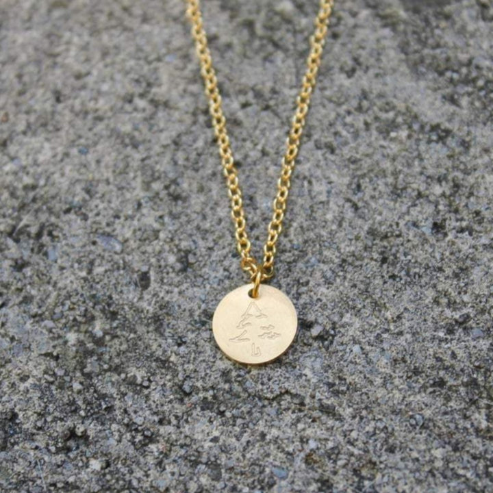 A gold necklace with a gold disc pendant with a tiny pine tree engraved by Vintage Acorn