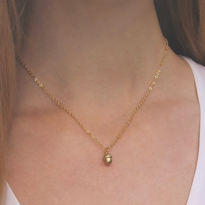 Woman Wearing Tiny Gold Acorn Necklace by Vintage Acorn