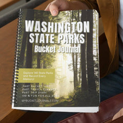 a person holding a coil bound Washington state parks bucket journal