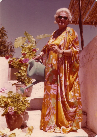A smiling woman in sunglasses and a glorious yellow/pink/orange caftan is standing in the sun, watering the plants on her patio garden with a green watering can. The photo looks to be from the mid-seventies.