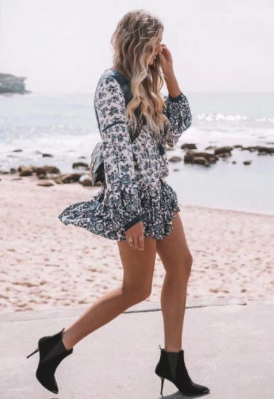 a woman wearing Vintage Floral V Neck Mini Dress walking on the beach in black high heels.