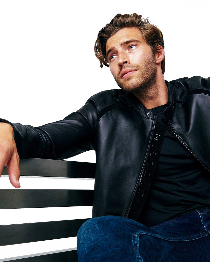 The MAVEN Leather Jacket in A man sitting while wearing a cadogan men's black leather jacket