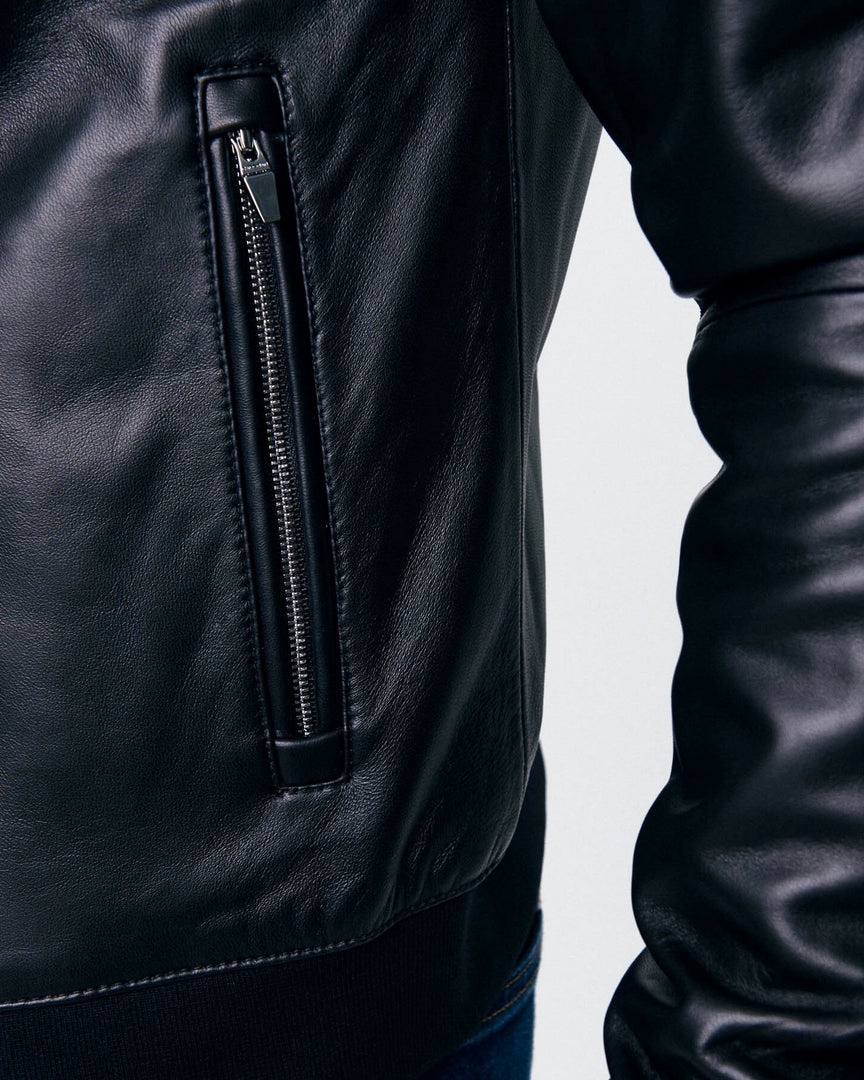 The front silver zipper and ribbed hemline of the CADOGAN Leather Jacket
