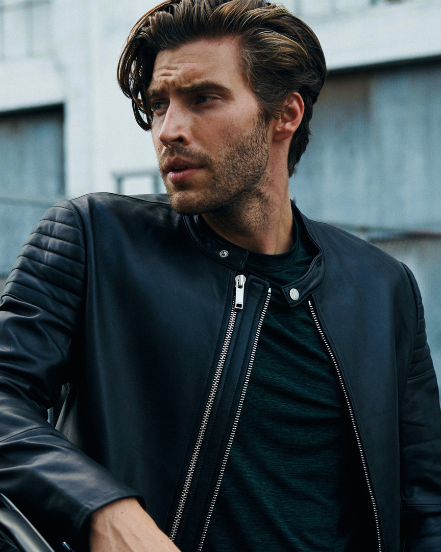 A man leaning against a car in the XANDER Men's Biker Jacket