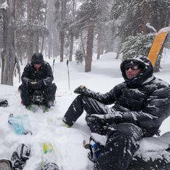 a stormy day, two guys sitting on their backpacks in a snow storm, with snow piling up on them