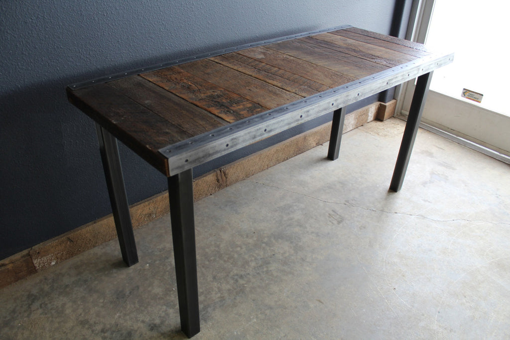 custom industrial dining table with raw steel trim and straight steel legs