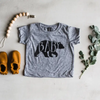 "Grey T-shirt with black grizzle bear outline containing the word ""Baby"", pictured with a silicone pacifier clip and a pair of booties"