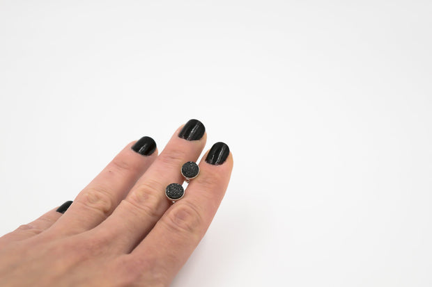 black druzy stud earrings in sterling silver shown in hand
