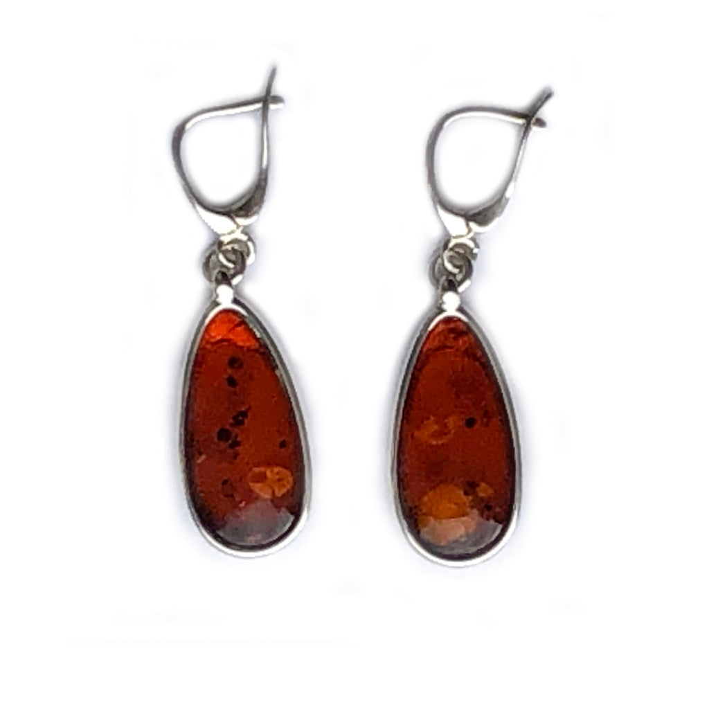 The Amber Centre. This beautiful pair of cognac amber earrings are set in a simple plain Sterling silver surround and suspended on very secure hooks that fasten at the back of the ear. The amber has some lovely inclusions and a clarity that catch the light beautifully.  Each piece of amber measures approximately 20mm x 10mm.  Length of earring including hook 40mm.