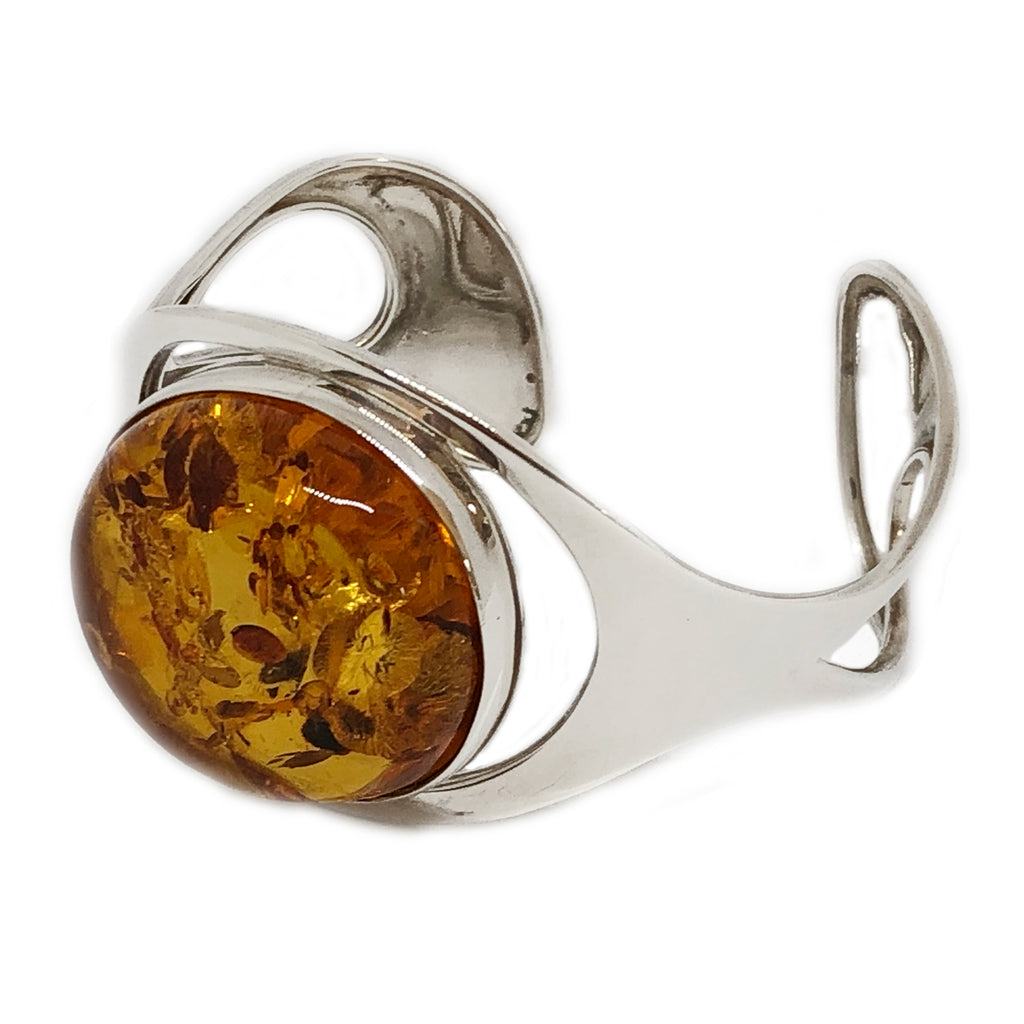 The Amber Centre. The beautiful amber sitting in this stunning Sterling silver bangle is absolutely exquisite. The inclusions vary from light to dark and the amber itself has a clarity which reflects the light. This is a piece of jewellery you will never tire of.  Amber measures 35mm x 30mm. Silver bangle is open at the back and slips over your wrist from the narrowest part on the side.