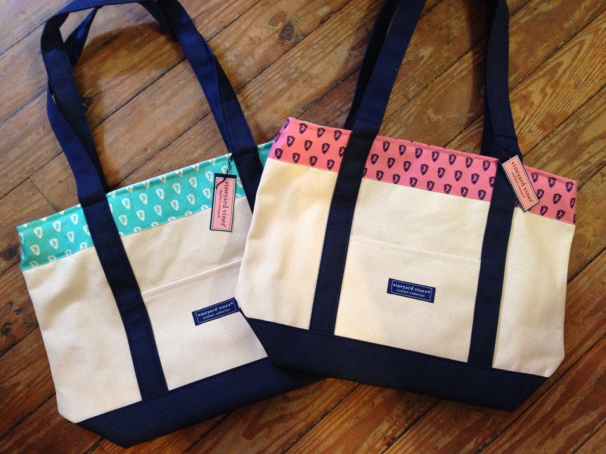 two canvas tote-bags: one has a baby blue section with a pattern of white lion shields and the other tote-bag has a pink section with navy lion shields. the handles are dark blue