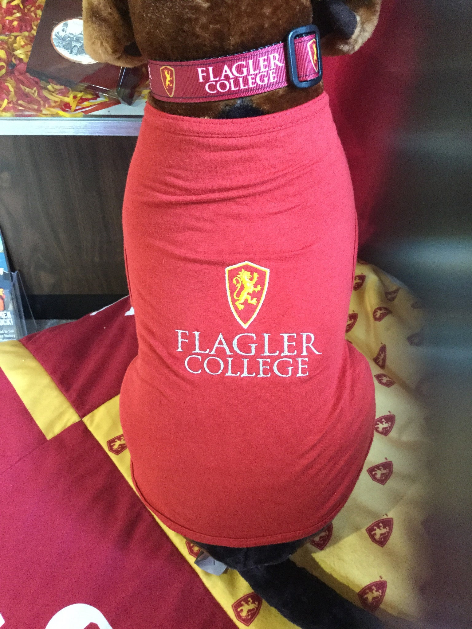 red dog shirt with Flagler college embroidered in white and shield embroidered in yellow and red