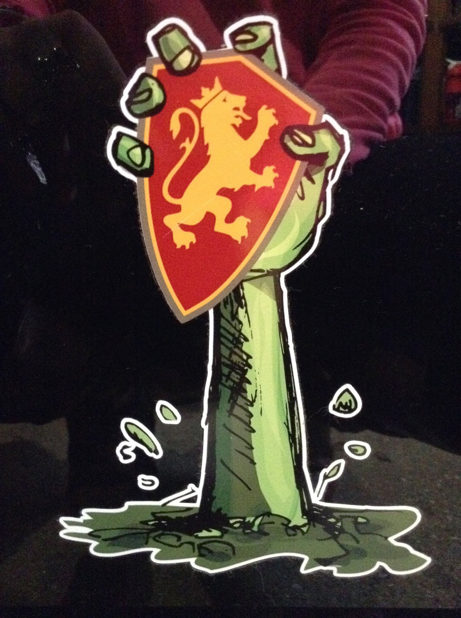 stick of green zombie hand grabbing gold and red lion shield