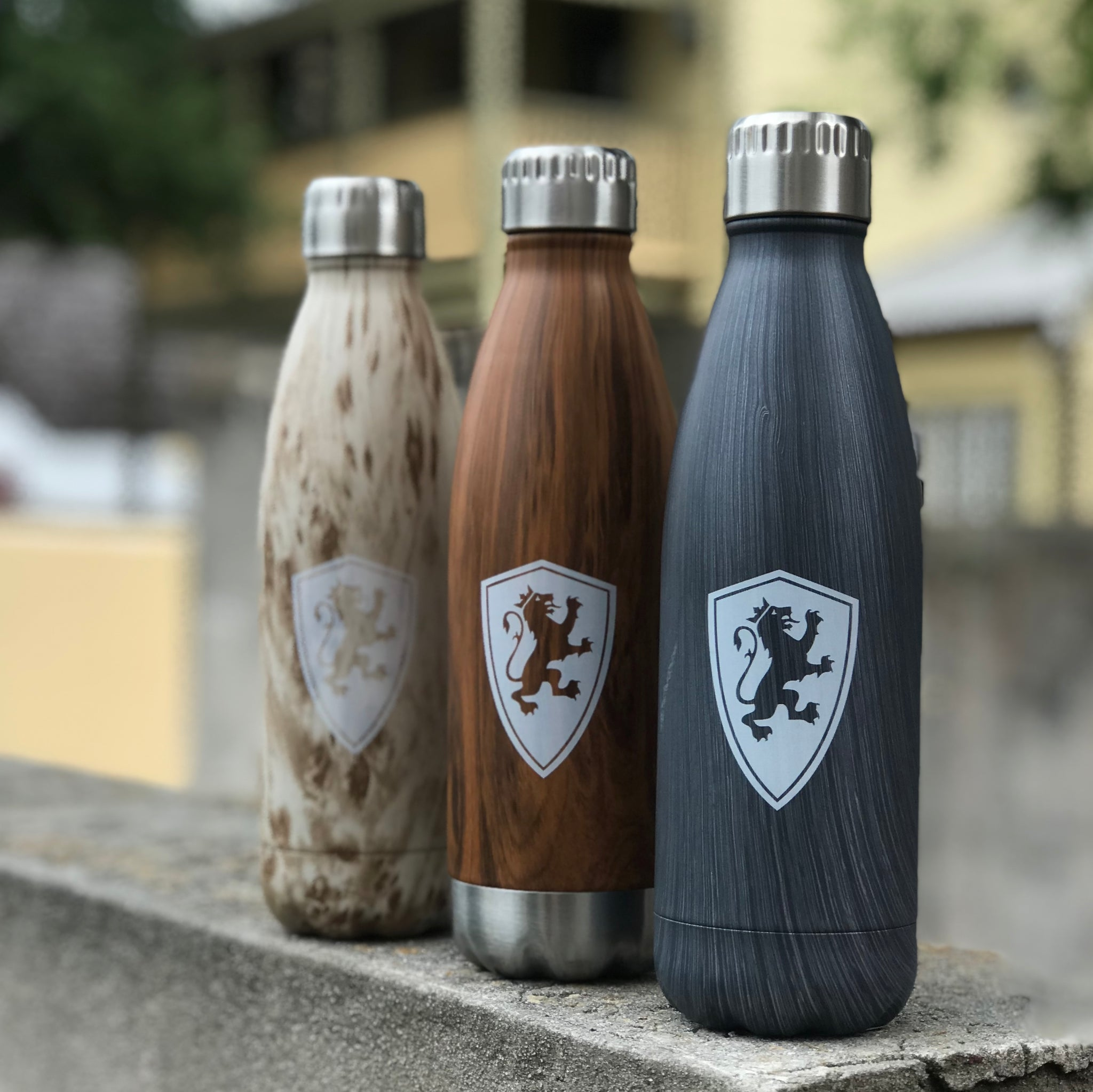 three Woodtone Flagler water bottle, one is light wood, second is dark wood, and last is grey. All have white lion shield printed on it and they all have a silver lid