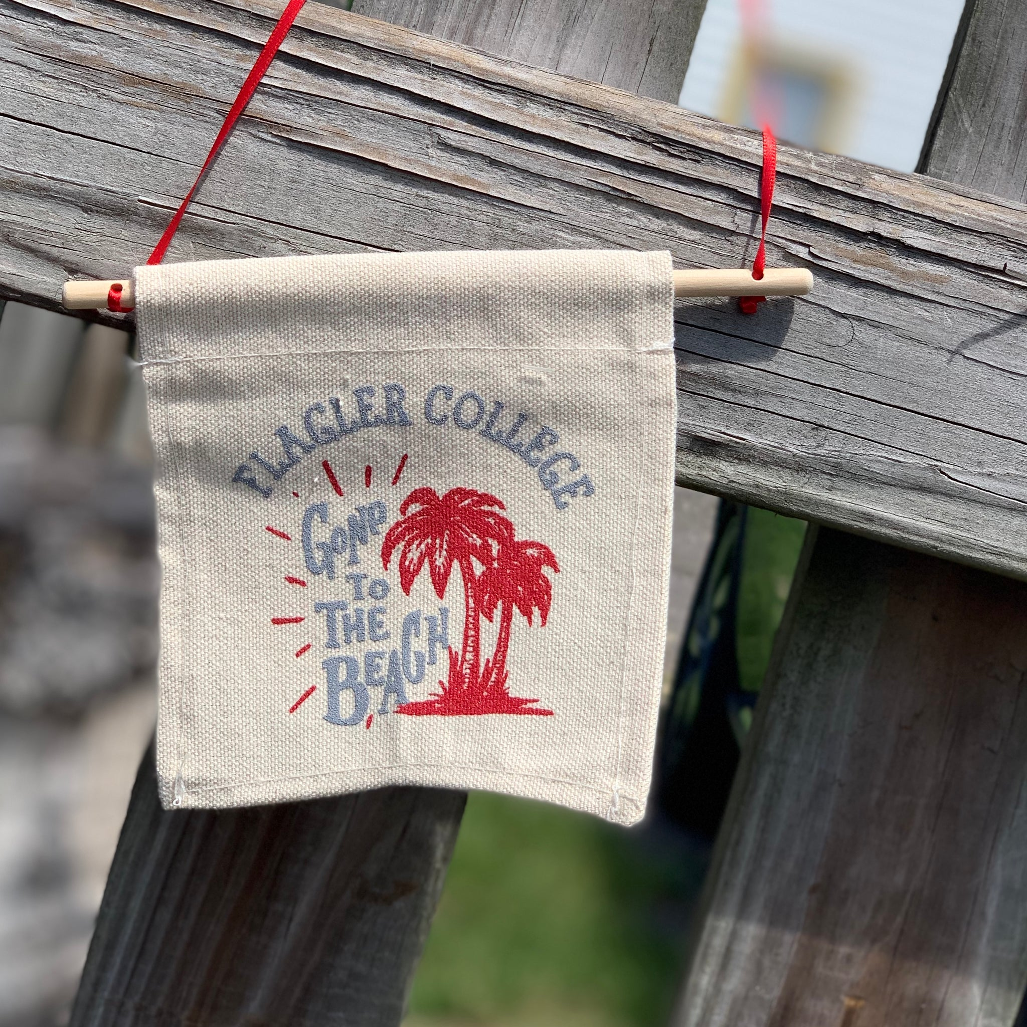 """Gone to the Beach"" canvas sign with red palm trees"