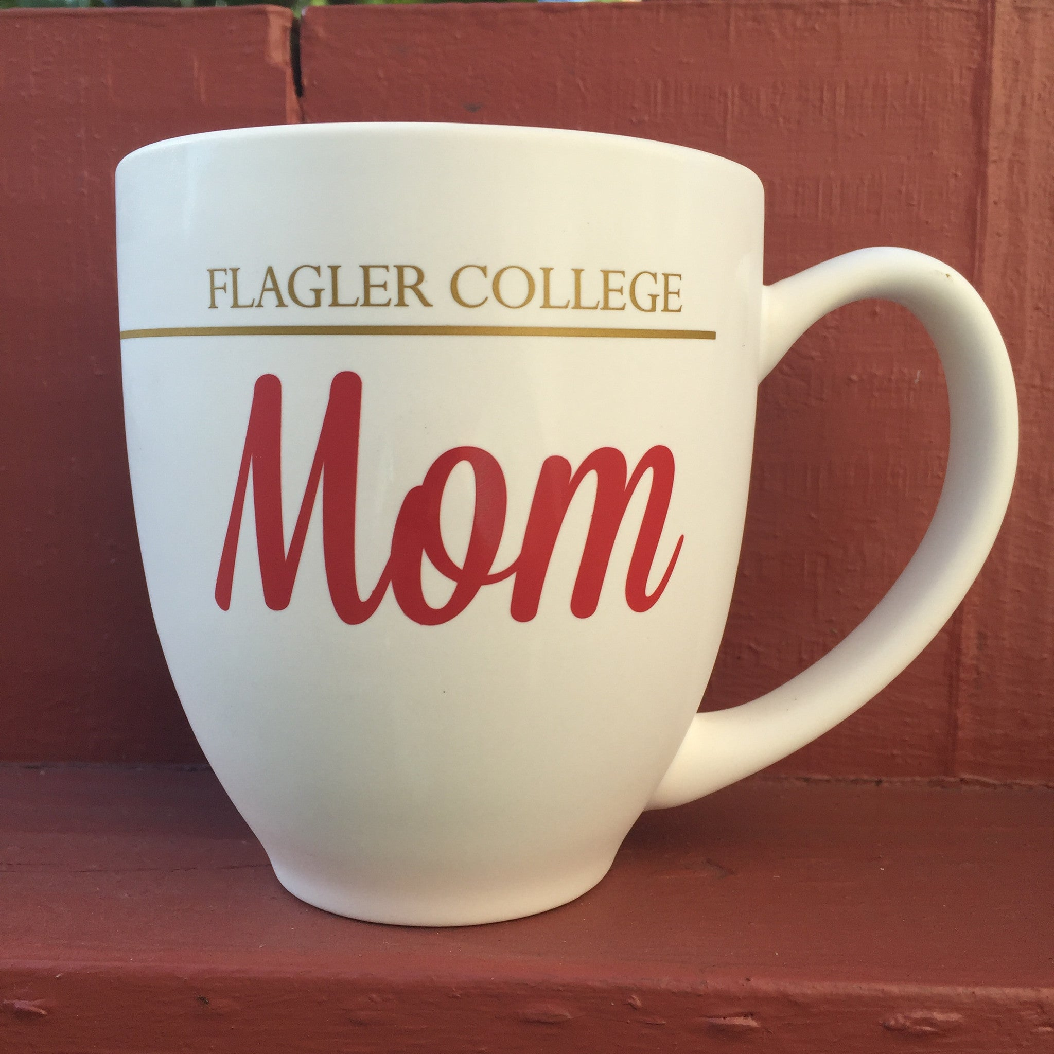 12 oz white mug with Flagler college printed in gold and mom printed in red