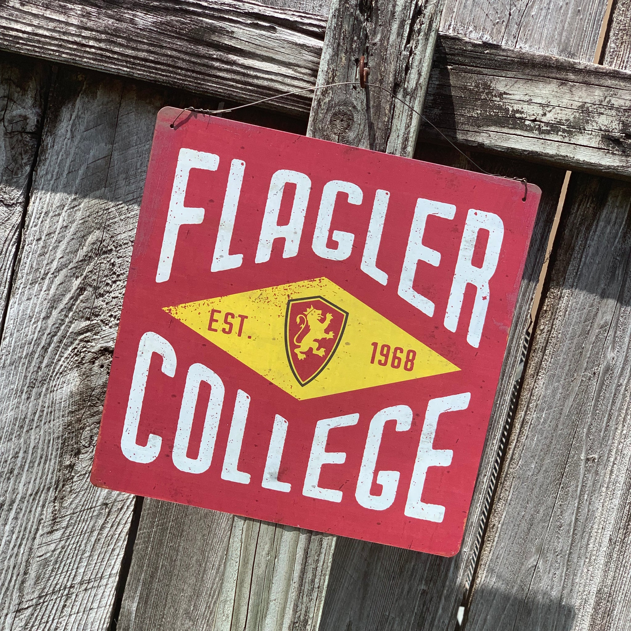 "red, white and yellow sign with flagler at top and college at bottom in white. in the middle, there is a diamond with a red lion shield and ""est 1968"""