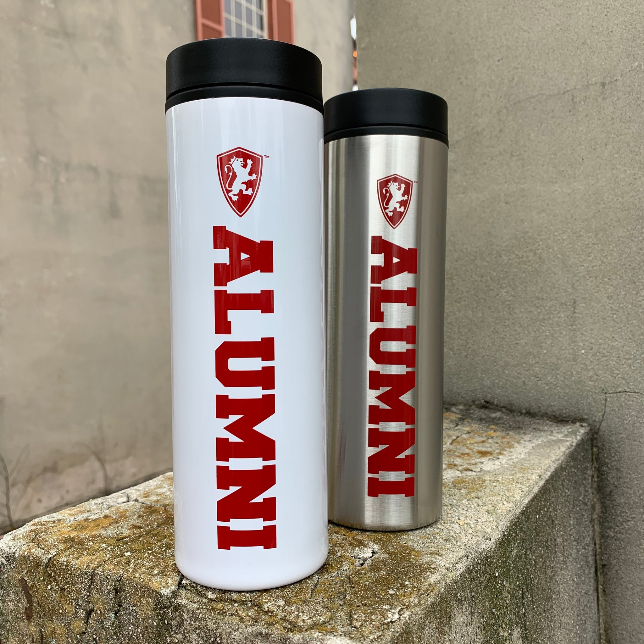 two 16 oz tumbler one white and the other is silver. shield and alumni printed in red on side of tumbler. lid is black
