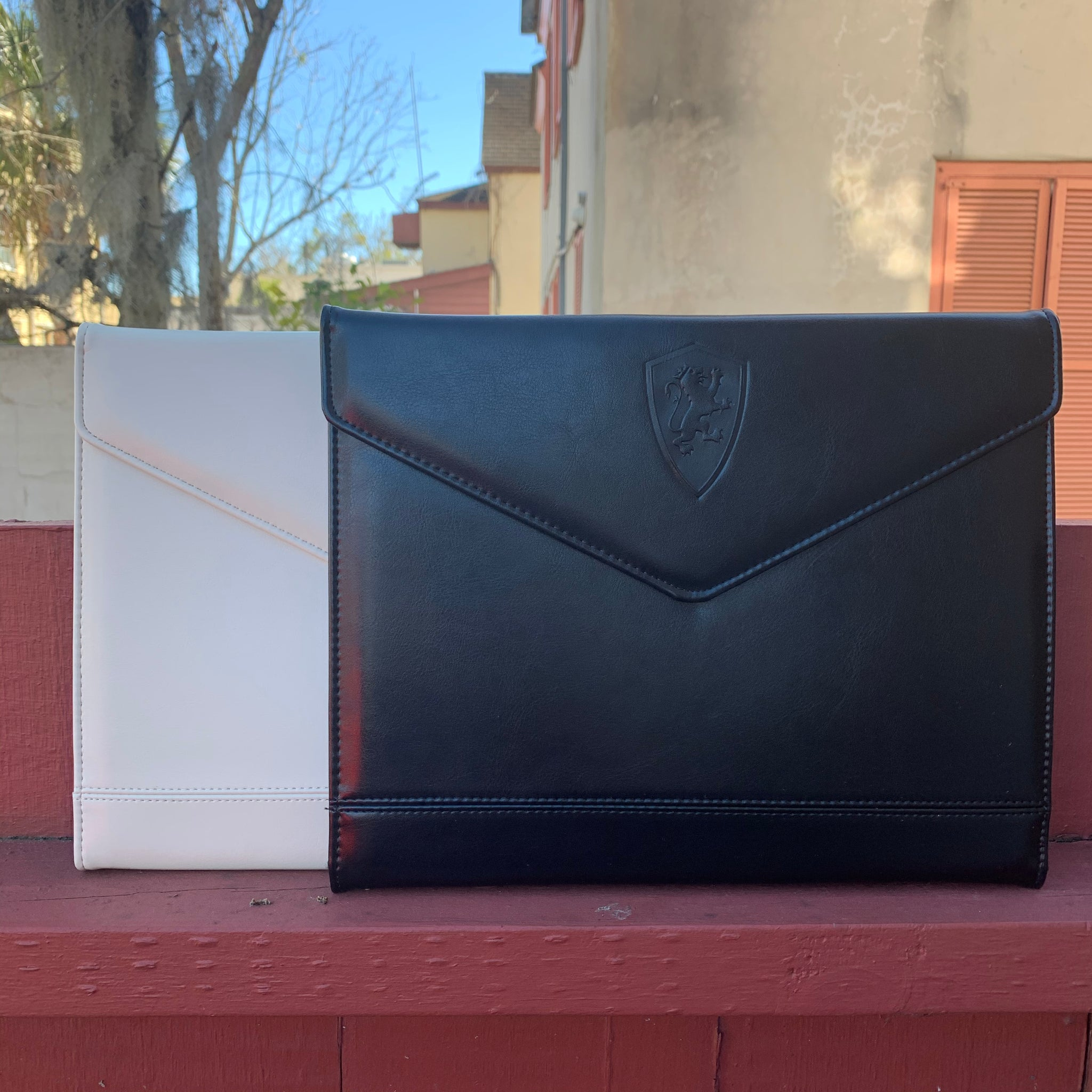 Two tri-fold padfolios; one white and the other black. they have a magnetic closure with a shield logo imprinted on them
