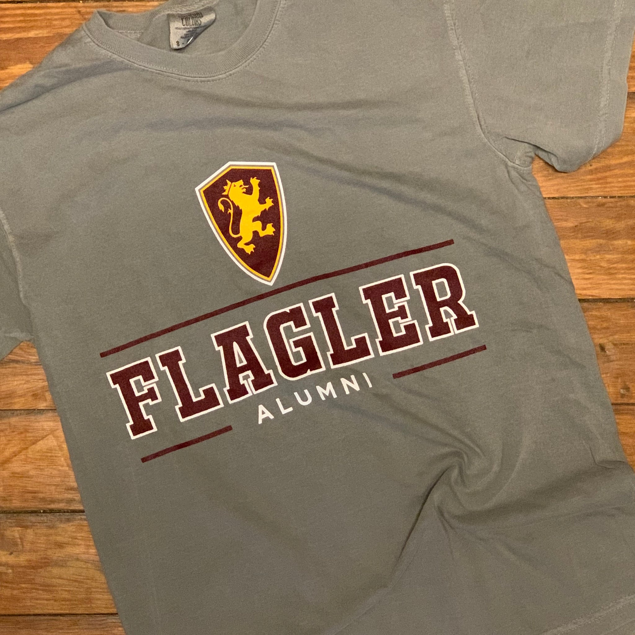 Grey short sleeve shirt with shield printed in yellow and red with white outline. red line underneath with Flagler printed in red with white outline. Alumni printed under in white. All on front of shirt
