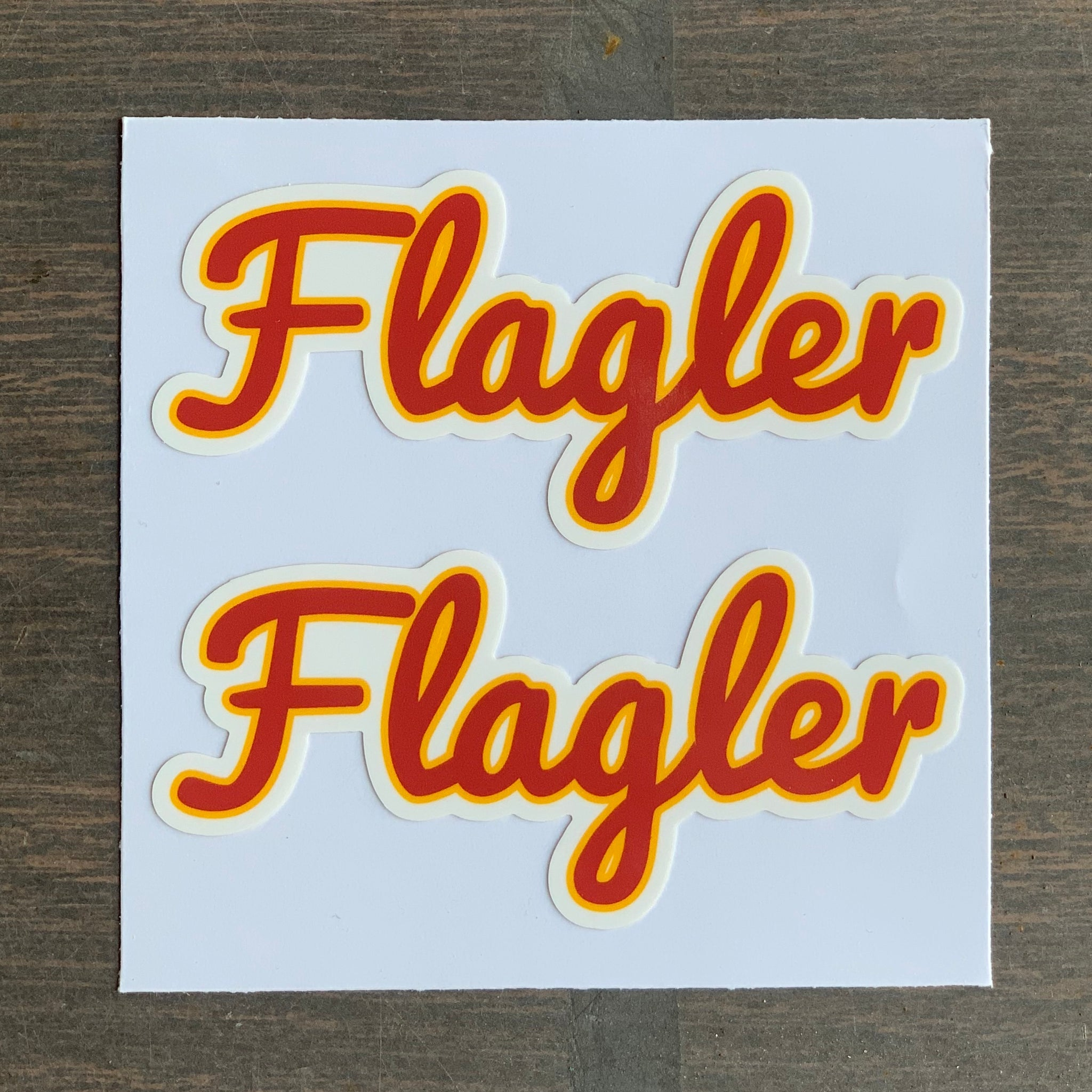 two pack of red and yellow cursive Flagler stickers
