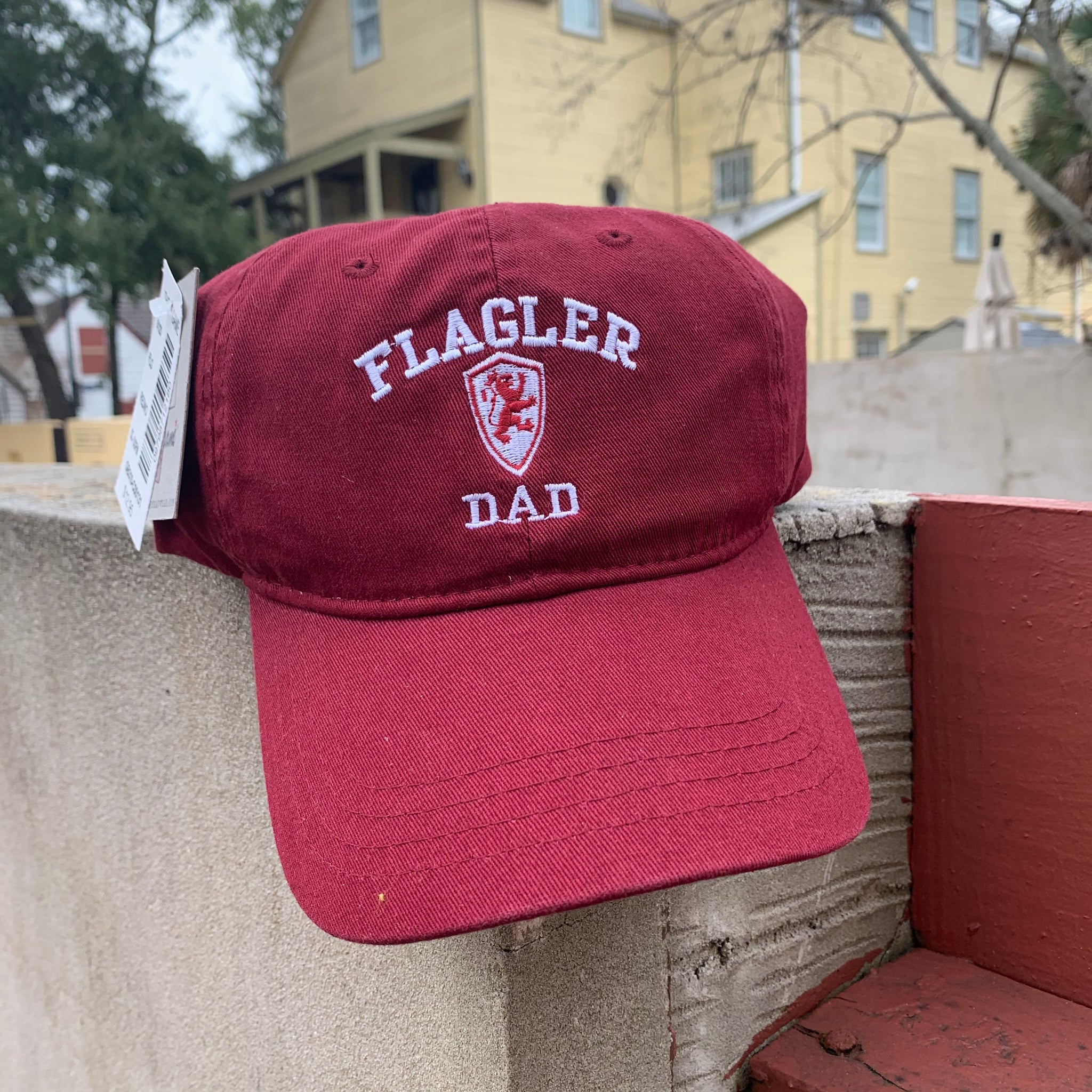 red hat with flagler, a lion shield, and dad embroidered in white in middle