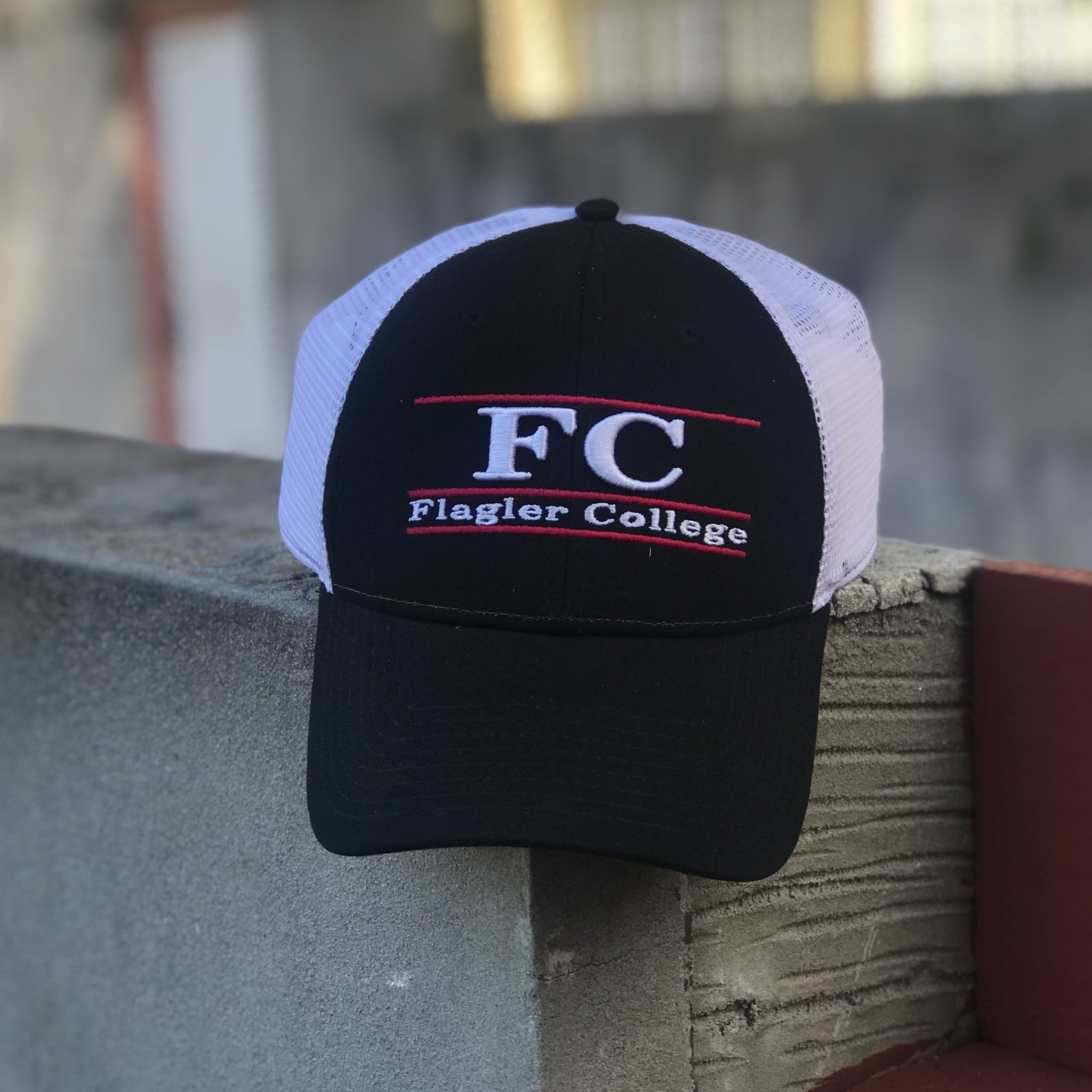 black front and white mesh in the back. FC and Flagler college are embroidered in white with red lines underlining words